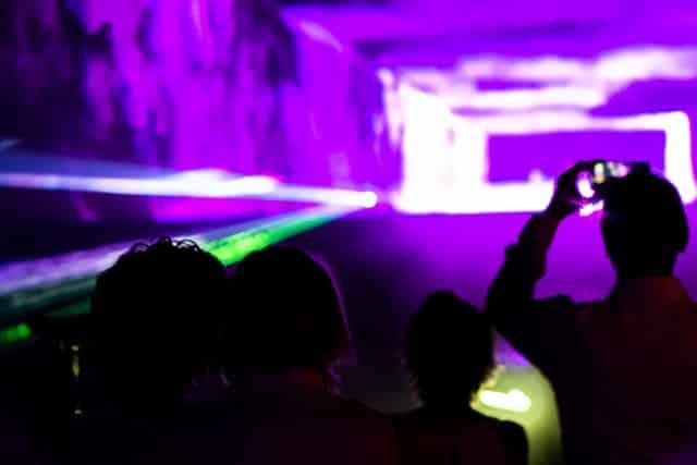 Mensch fotografiert eine Lasershow